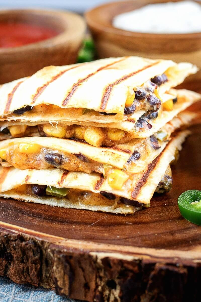 Corn and Black Bean Vegetarian Quesadillas stacked onto a natural wood platter