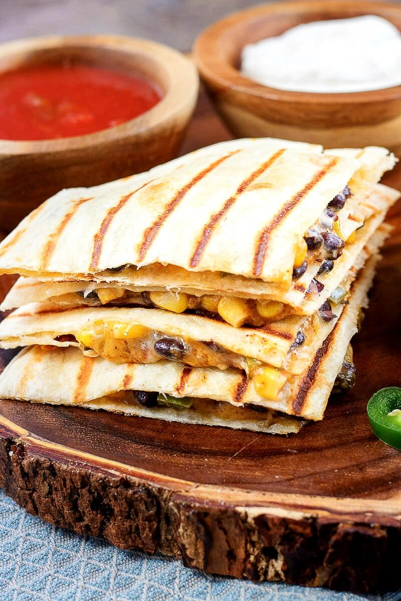 vegetarian quesadillas filled with spicy corn and black bean mixture and cheese on a natural wood serving platter (with bark exterior)