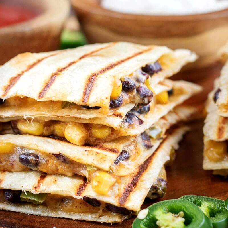 close up square image of vegetarian quesadillas filled with spicy black beans, corn, and cheese