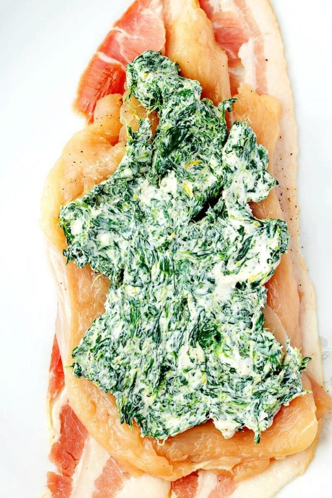 cream cheese and spinach filling spread onto a flattened chicken breast for a chicken rollups recipe