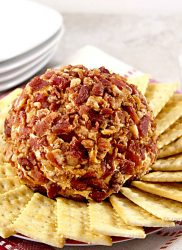 bacon covered chipotle cheddar cheese ball surrounded by crackers