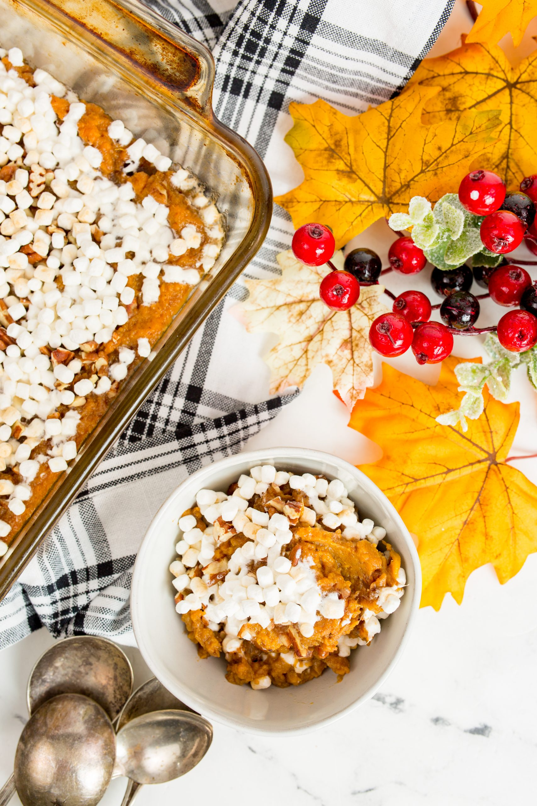 Overhead shot of sweet potato casserole with bowl and fall leaves