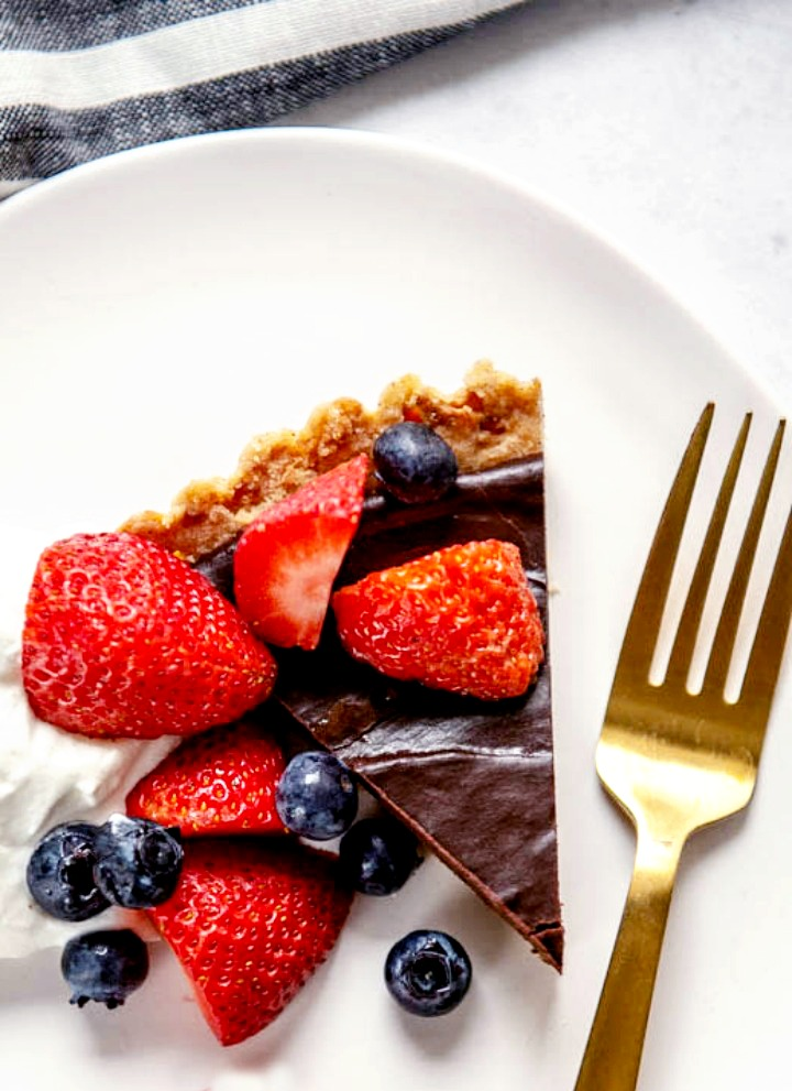 slice of dessert tart with dark chocolate ganache