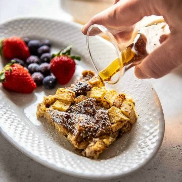 pouring syrup over French toast casserole