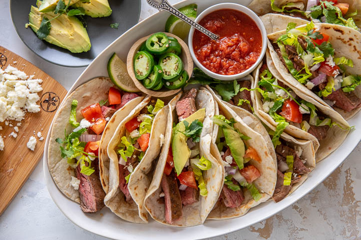 marinated steak tacos on a platter with taco toppings