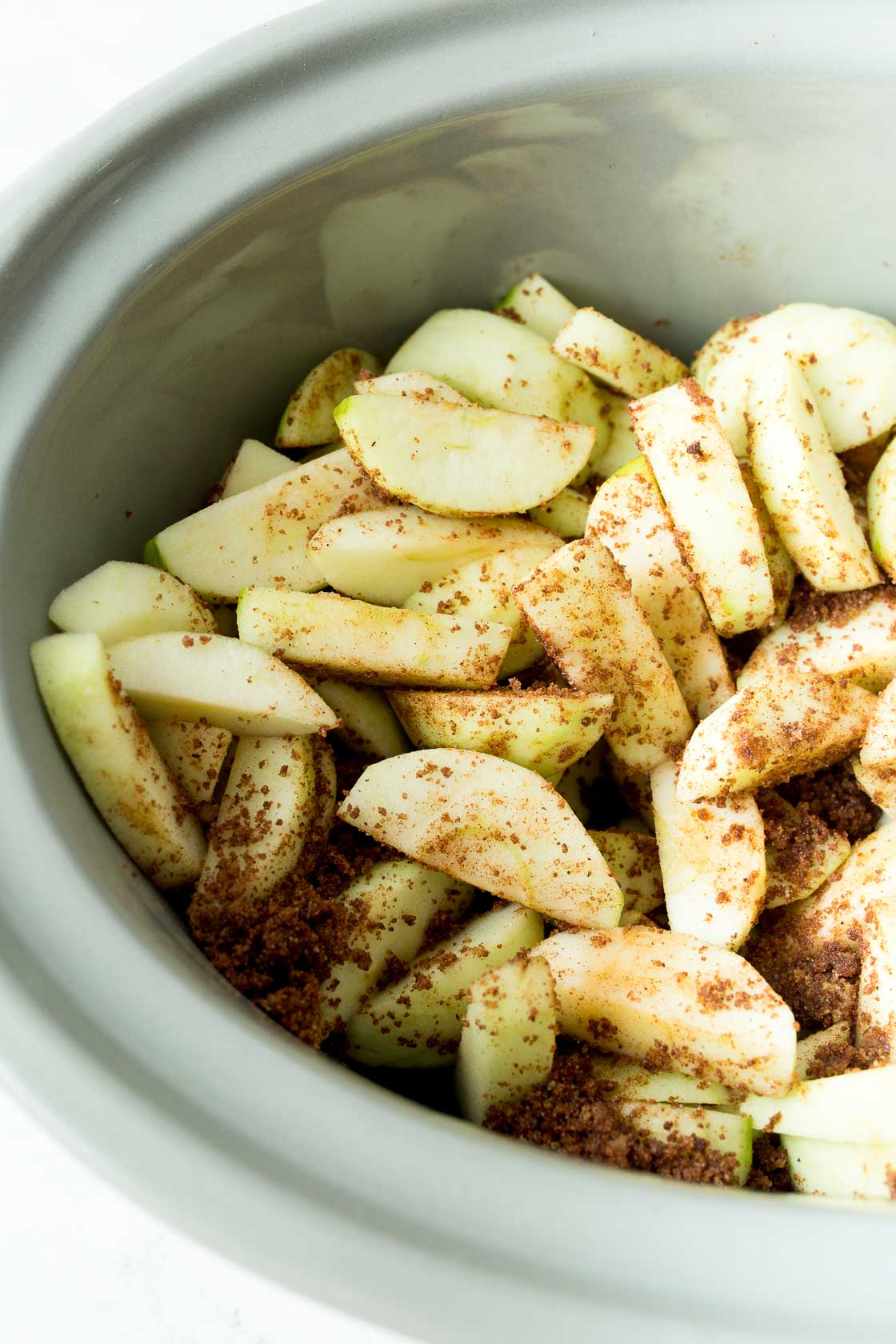 Sliced apples in slow cooker before cooked
