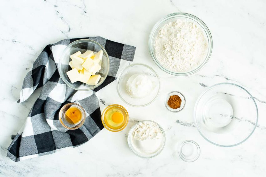 Individual ingredients for homemade crust are laid on a white marble countertop.