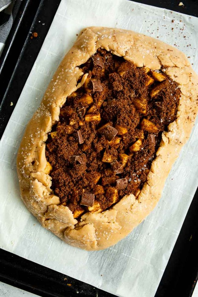 The edges of the pie crust are folded up in a rustic fashion, slightly over the apple galette filling.