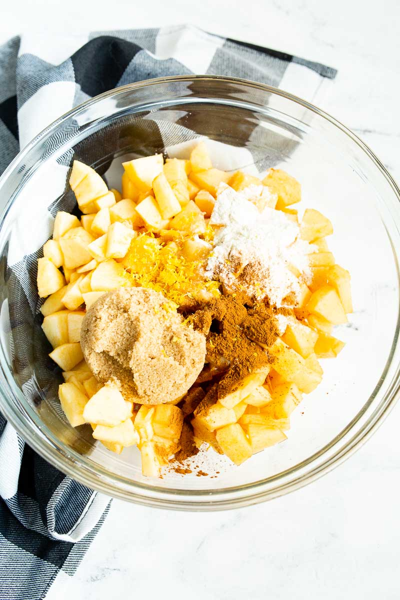 Ingredients for an apple galette filling are combined in one large bowl.