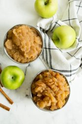 two bowls of chunky slow cooker applesauce with apples around